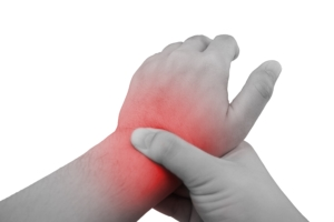 Pain in a wrist. holding hand to spot of wrist pain.