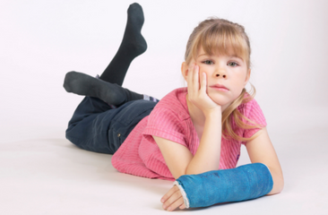 Girl lying on floor with arm in a blue cast.